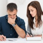 Couple calculating financial budget for home purchase