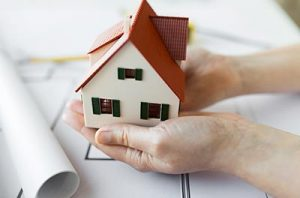 Hands Holding a Small Model House on Top of NY Fixed Rate Mortgage Paperwork