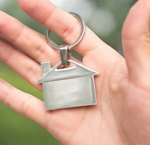 Hand holding a keychain shaped like a house