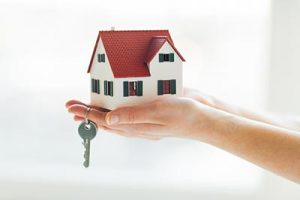 Hands holding a small house and the key to a new home