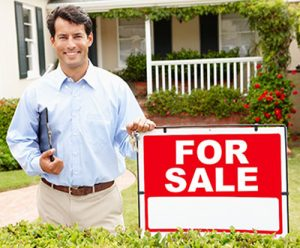Real estate agent in front of a house for sale