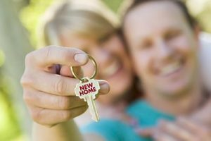 First time home buyers holding the keys to their new home after navigating the mortgage process