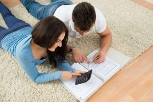 young couple reviewing financial documents and calculating mortgage payment