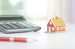 A calculator, a small house and a pen sitting on a white table