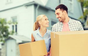 young couple with moving boxes outside of their new home that they secured with a non-conforming mortgage
