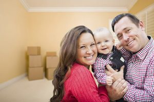 Young family in a new home with moving boxes in the background