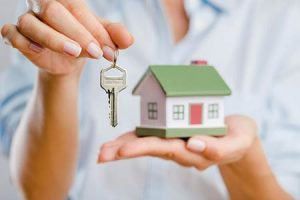 close up of woman holding house keys in one hand and a home model in the other