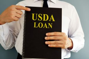 USDA Loan concept. Man holding book.