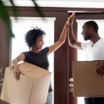 Happy young African American couple celebrate moving into their first home
