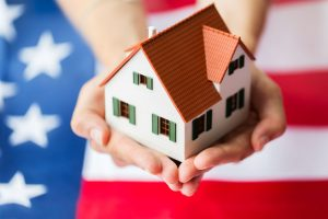 close up of hands holding living house model over American flag