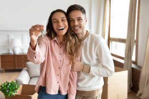 Happy young family couple holding key to new home purchased with FHA loan