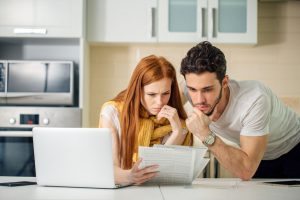 young couple looking at documents to determine what's covered in their monthly mortgage payment