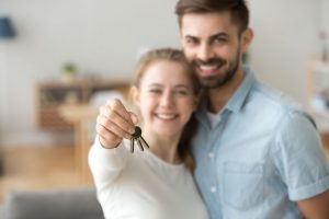 Happy young married couple holding keys to new house after navigating the mortgage process