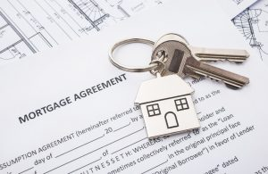 subprime mortgage loan agreement application with house shaped keyring